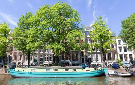 The city view of Amsterdam Amstel canal, typical dutch houses and boats, Holland, Netherlands.