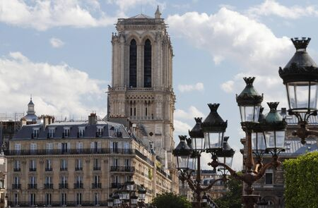 View of the bell towers of Notre-Dame de Paris cathedral and traditional street lamps in the foreground.