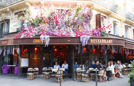 The vintage cafe Comptoir decorated with flowers , Paris, France