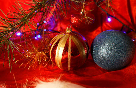 Two christmas balls on red background with fir branch.