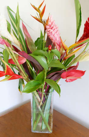 The colorful tropical flowers bouquet arrangement on wooden background. Zdjęcie Seryjne
