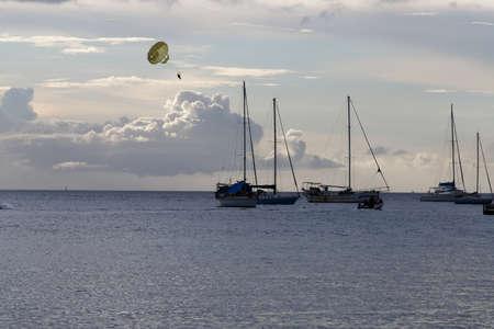The catamaran and sailboats anchored in waters of caribbean beach.