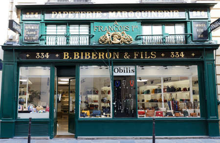 The vintage facade of ancient boutique located at Saint Honore street in Paris. Inscription in French: Stationery shop, Leather shop.