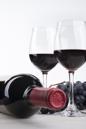 white wine: Bottle of red wine and two glasses on white background