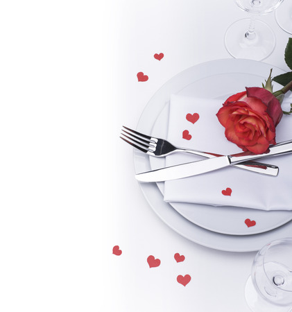 Festive restaurant table set for Valentines with rose and hearts