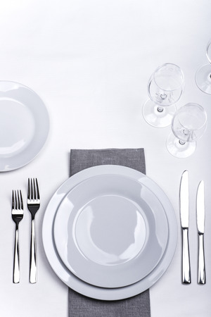 Plates, forks, knives and glasses on white tablecloth with grey napkin