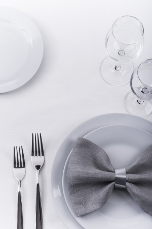 Plates and silverware with grey napkin on white tablecloth photo