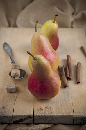 Flamingo pears on wooden surface, cinnamon and sugar