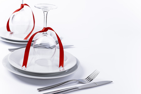 Wine glasses turned upside down with red decoration as background for invitation and menu