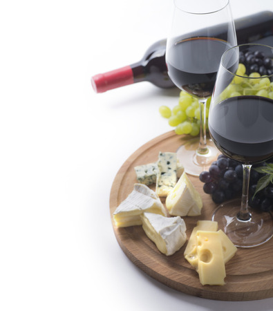 Two glasses of red wine, bottle, cheese and grapes on white background