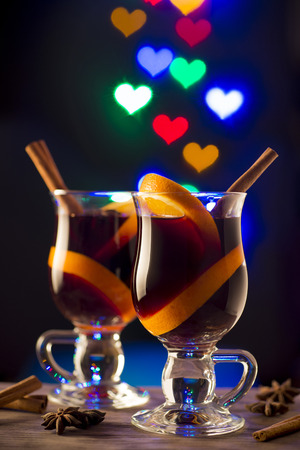 Glasses with mulled wine on dark background with light hearts photo