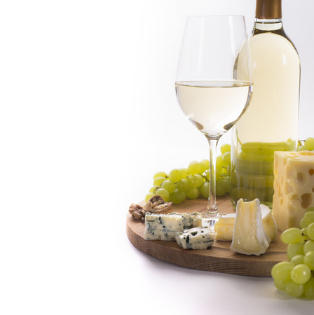 White wine, cheese, nuts and grapes for snack on white background photo