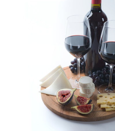 Two glasses of red wine, goat cheese and fig on white background photo