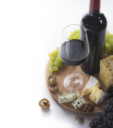 aperitif: Red wine, glass, grapes, cheese and nuts on white background