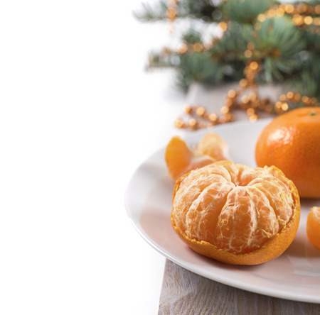 citrus family: Mandarins on a plate with fur tree at the background - new year style Stock Photo
