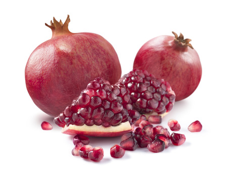 Two whole pomegranates plus piece and seeds isolated on white background as package design elements