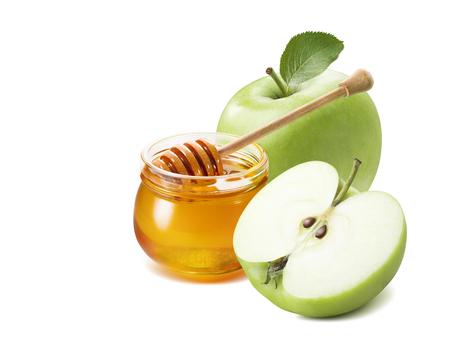 Maçã verde metade e pote de mel para o ano novo judaico isolado no fundo branco para design de cartaz Foto de archivo - 85110517