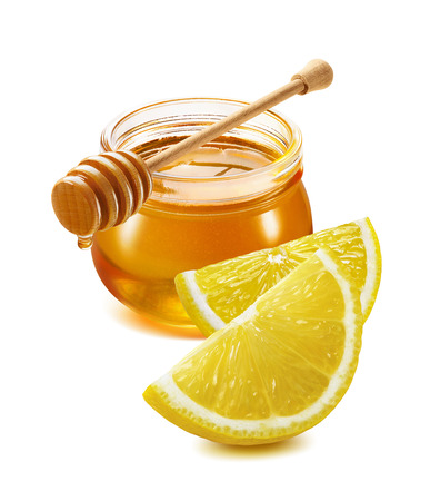 Remedy for flu and cold - honey jar, lemon quarters isolated on white background