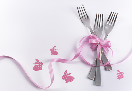 Silverware on white with pink ribbon as background for menu and invitation
