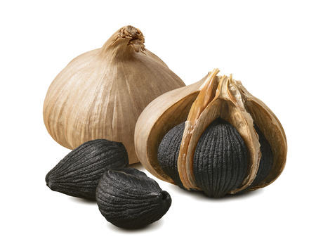 Black garlic bulbs and cloves isolated on white Standard-Bild