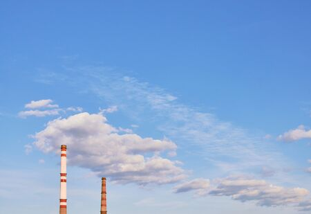 Chimneys of thermal power plant in the blue sky with clouds.