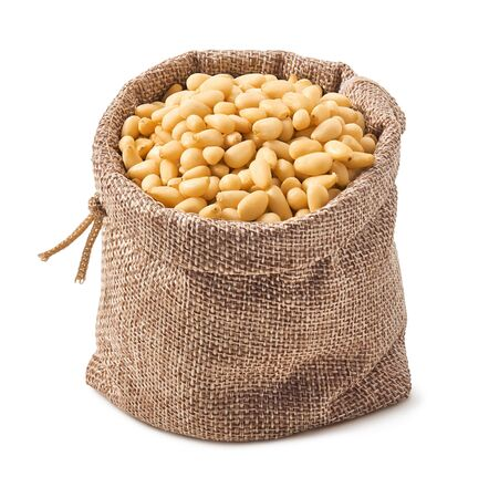 Pine nuts in burlap bag isolated on white