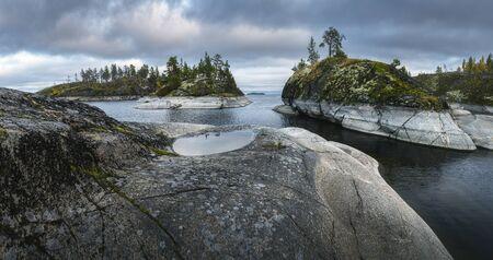 Pfütze auf einem Felsen im Vordergrund. Küstennadelwälder bedecken felsige Inseln. Nordische Landschaft Standard-Bild
