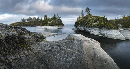 Puddle on a rock in the foreground. Coastal conifer forests cover rocky islands. Nordic landscape 写真素材