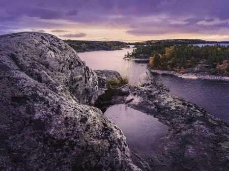 Puddle on a rock in the foreground. Purple colors. Conifer forests cover rocky islands. Nordic landscape. Dramatic sky