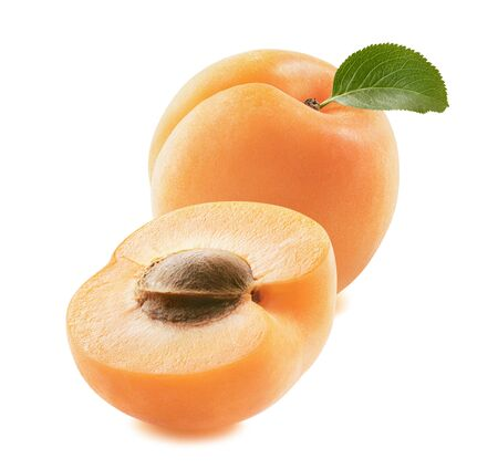 Fresh apricot with a green leaf and half isolated on white