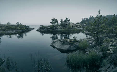 Small forested rocky islands in the fog. Scenic view of the lake. Horizontal layout