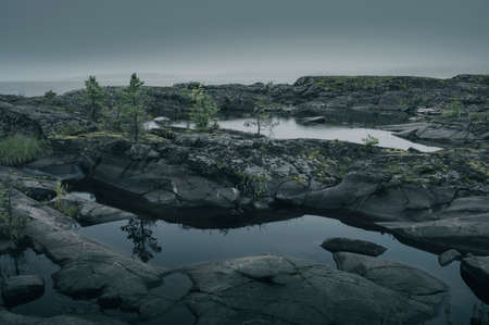 Water puddles in the rocky shore. Scenic view of a foggy island. Zdjęcie Seryjne
