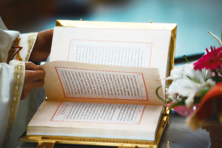 The Book of the Gospel is open for reading in the hands of the priest at the wedding.