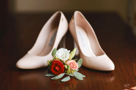 wedding accessories bouquet red, white and pink flowers for groom and beige shoes on dark wooden background.