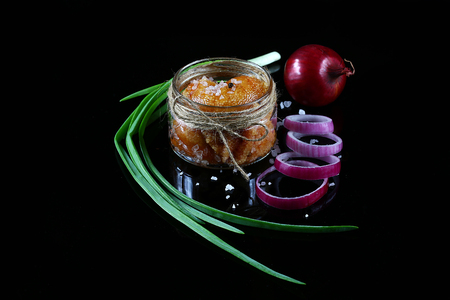 Delicious caviar, roe close up, pike caviar in a transparent jar, purple onion cut into rings on a black background, top view, set.