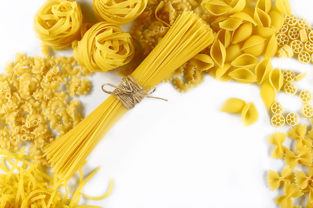Food concept - various uncooked, raw Italian pasta on white background, top view, place for text, set.