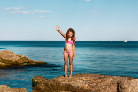 young curly girl in a pink swimsuit relaxing on the rocks on the beach, the Black Sea, Odessa, Ukraine, a place for text, a set.
