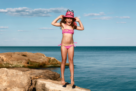 young curly girl in a pink swimsuit relaxing on the rocks on the beach, jumps in a hat Black Sea, Odessa, Ukraine, place for text set. Stock Photo