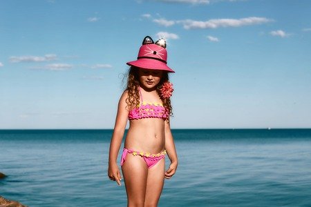 young curly girl in a pink swimsuit relaxing on the beach in the hat, Black Sea, Odessa, Ukraine, place for text set.