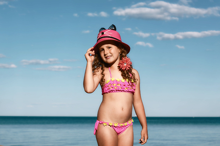 young curly girl in a pink swimsuit relaxing on the beach in the hat, Black Sea, Odessa, Ukraine, place for text set. Stockfoto - 97031661