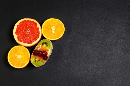 Variety of fruits grapefruit, oranges, kiwi, mint, cake, sweet fruit dessert bunched, together on a shale board, the concept of healthy eating, copy space, top view set.