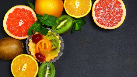 Variety of fruits grapefruit, oranges, kiwi, lemon, mint bunched together on a shale board, the concept of healthy eating, copy space, top view set. 版權商用圖片