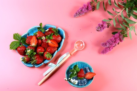 two blue plates of fresh strawberries, ice, mint, pink flowers, decorative spoon isolated on pink background with copy space. View from above, set.