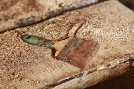 dirty used paint brushe on the background of wooden boards with sawdust.