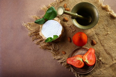 Camembert or brie cheese circle, decorated with basil and pieces of tomatoes, spice dish, on old ragged fabric, top view image with copy space, set. Stock Photo