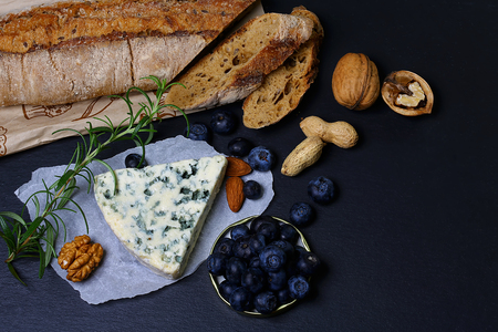 Cheese market - camembert, salty blue cheese and gauda tasting with berries, nuts, snack, big size resolution. Food banner for text or design. Side view photo.