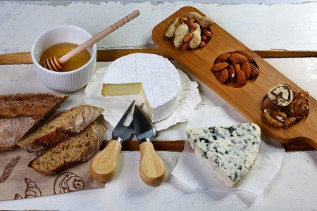 Ingredients for the bruschetta: cheese camembert, DorBlu, salty blue cheese with mold, nuts and honey on light background.