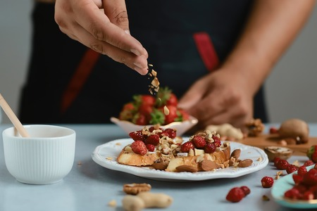 Sweet sandwiches with strawberries, cheese, camembert, brie, nuts and honey on the whole grain bread bruschetta cooking by chef hand on light background.