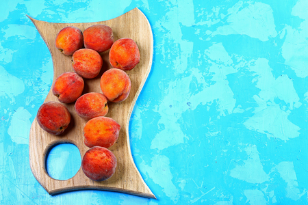 ripe peaches on a wooden board. blue background. Fresh peach concept. Flat lay. Copy text. Stock Photo