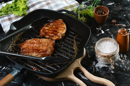 grilled beef fillet steaks with herbs and spices on dark background. Food concept.